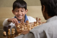 boy plays chess with father and smiles (horizontal) - Alex Mares-Manton