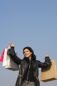 woman with shopping bags raised in air - Alex Mares-Manton