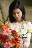 woman looks down at bouquet of flowers - Alex Mares-Manton