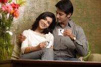 couple hold up tea cups, man looks at woman - Alex Mares-Manton