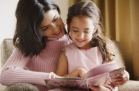 mother reads story book to her daughter - Alex Mares-Manton