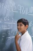 boy at chalkboard, finger on chin - Alex Mares-Manton
