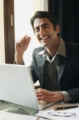business man working at laptop, laughing - Alex Mares-Manton