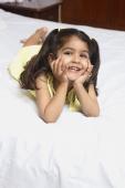 Girl lying on bed, chin in hands - Manoj Adhikari