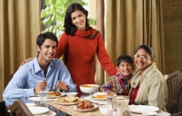 woman stands over dinner table with smiling family - Alex Mares-Manton
