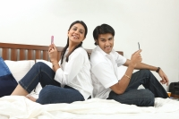 Couple back to back on bed - Deepak Budhraja