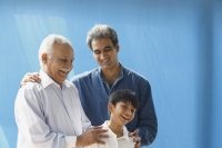 Grandfather, father, son laughing, blue background - Manoj Adhikari