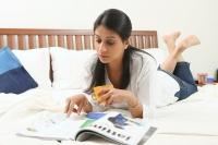 Woman reading on bed - Deepak Budhraja