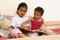 Sisters reading story book - Deepak Budhraja
