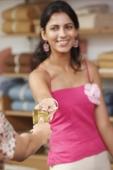 woman handing gold card to cashier - Vivek Sharma