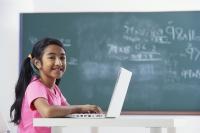 girl working at laptop, smiling at camera - Alex Mares-Manton