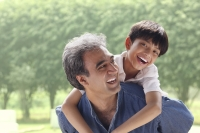 Father with son on his back, son smiling at camera - Manoj Adhikari