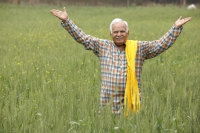 farmer in field, hands in air - Manoj Adhikari