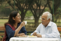 senior couple having coffee outdoors - Manoj Adhikari