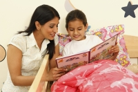Mom reading story to daughter in bed - Deepak Budhraja
