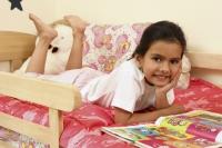 Girl in bed with book - Deepak Budhraja