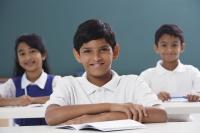 three students smiling at camera, boy in center - Alex Mares-Manton