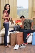 woman showing boyfriend her shopping purchases - Vivek Sharma