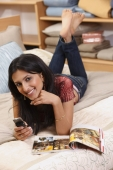 young woman on bed checking text messages - Vivek Sharma