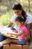 Mother and daughter with book - Deepak Budhraja