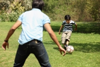 Father and son kicking soccer ball - Deepak Budhraja