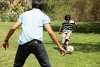 Father and son kicking soccer ball - Deepak Budhraja