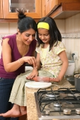 Mom and daughter making bread - Deepak Budhraja