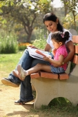 Mother and daughter reading on park bench - Deepak Budhraja
