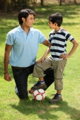 Father and son with foot on soccer ball - Deepak Budhraja