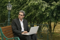 man with laptop on bench - Manoj Adhikari