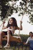 mother pushing girl on swing - Manoj Adhikari