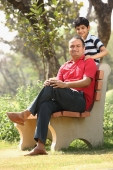 Father on bench, son standing - Deepak Budhraja