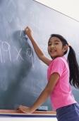girl working at chalkboard, facing camera (vertical) - Alex Mares-Manton