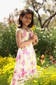 Little girl standing with yellow flowers - Deepak Budhraja