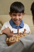 boy plays chess with father and smiles (vertical) - Alex Mares-Manton