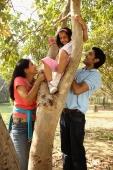 Parents helping daugther climb a tree - Deepak Budhraja