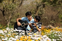 Father and son with guitar outside - Deepak Budhraja