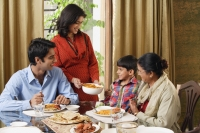 woman serves dinner to her family - Alex Mares-Manton