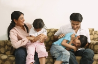 Family tickling on couch - Deepak Budhraja
