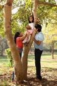 Family at park, daughter up tree - Deepak Budhraja