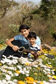 Father and son with guitar in park - Deepak Budhraja