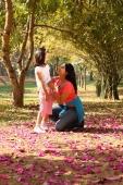 Mother and daughter in grove of trees - Deepak Budhraja