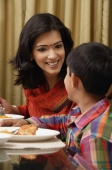 mother smiles to son at dinner table - Alex Mares-Manton