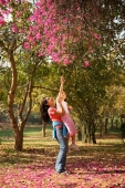 Mother lifting daughter up to tree - Deepak Budhraja