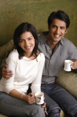 couple holding tea cups and smiling at camera - Alex Mares-Manton