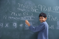 boy working at chalkboard, smiling at camera - Alex Mares-Manton