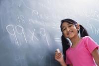 girl working at chalkboard, facing camera (horizontal) - Alex Mares-Manton
