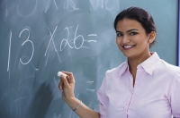 teacher smiling as she writes at chalkboard - Alex Mares-Manton
