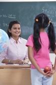 student holding apple for teacher - Alex Mares-Manton