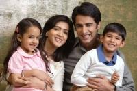 family of four smile at camera - Alex Mares-Manton